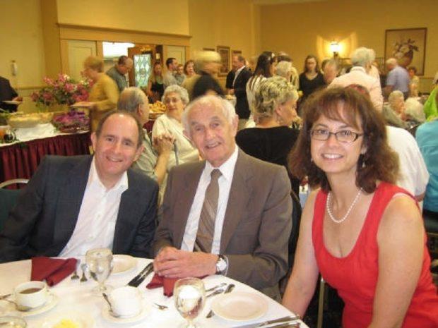 Deux hommes et une femme attablés pour un repas. D'autres personnes sont visibles à l'arrière-plan.