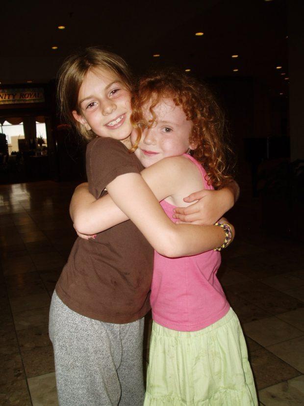 Deux fillettes posant en se faisant l'accolade.