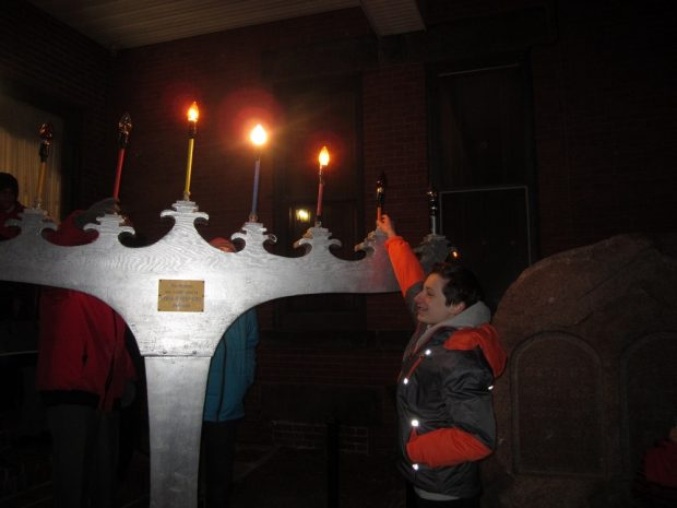 Grande menorah de Hanoukka peinte en gris dont certaines bougies sont allumées. Un adolescent lève le bras pour redresser une bougie.