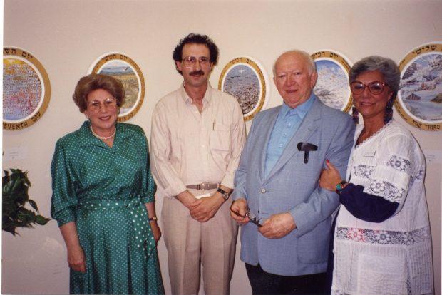 Deux hommes et deux femmes se tenant debout côte à côte. Des peintures sont visibles sur le mur derrière eux.