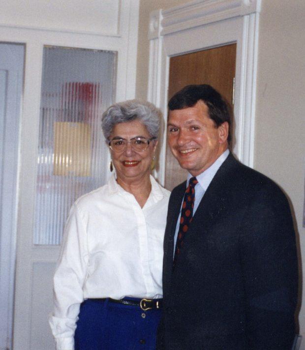 Une femme aux cheveux gris portant un chemisier blanc et un homme portant un complet sombre posant en souriant pour la photo.