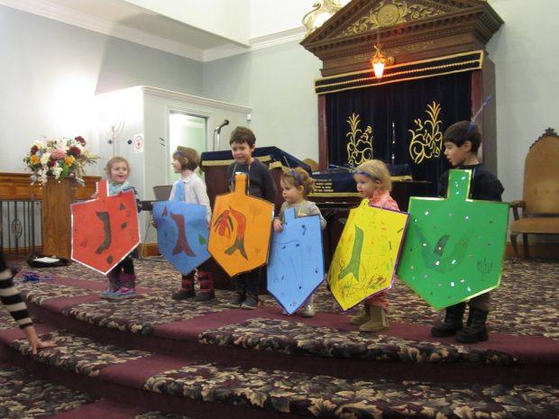 Six enfants sur une estrade devant la synagogue, chacun portant une toupie de Hanoucca en carton grandeur nature.