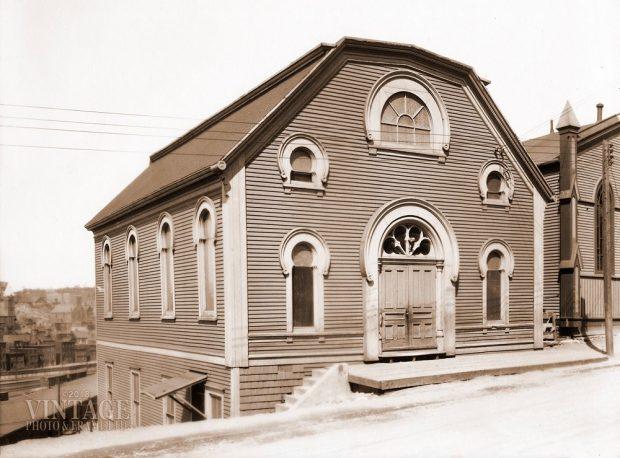 Immeuble en bois comportant une porte centrale et cinq fenêtres surmontées d'arcs arrondis.