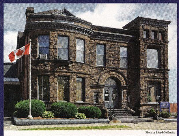 Grand immeuble en grès de deux niveaux doté de grandes fenêtres et d'un escalier menant à l'entrée; à gauche, un drapeau canadien hissé sur un mât.