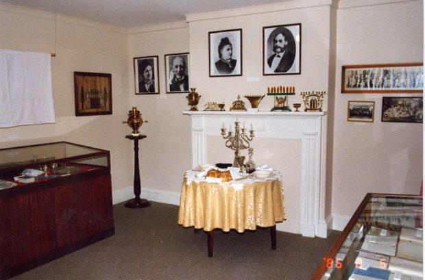 Salle d'exposition du Musée où l'on voit deux présentoirs vitrés, une table préparée pour un repas du Shabbat, un assortiment de menorahs de Hanoukka en laiton sur le manteau de cheminée et des photographies sur le mur.