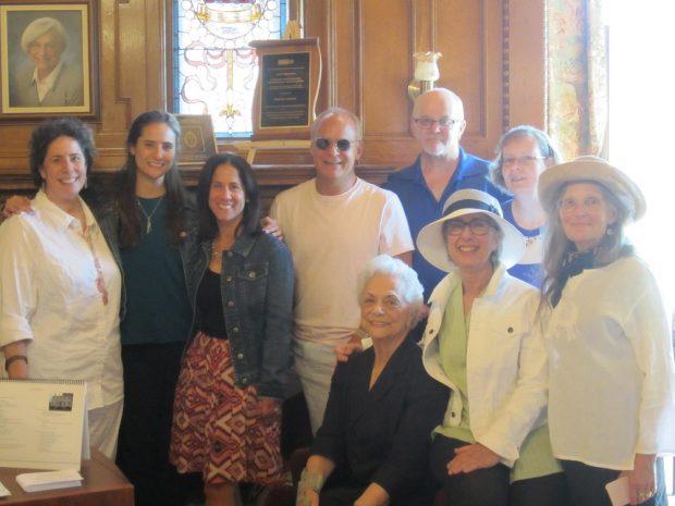 Sept femmes et deux hommes rassemblés dans une section d'une salle d'exposition au Musée historique juif.