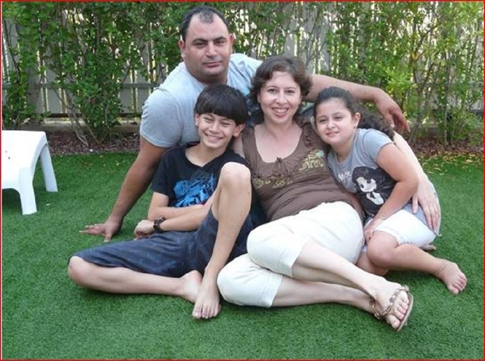 Portrait de famille non officiel : les parents et leurs deux enfants, un garçon et une fille, sont tous assis par terre.