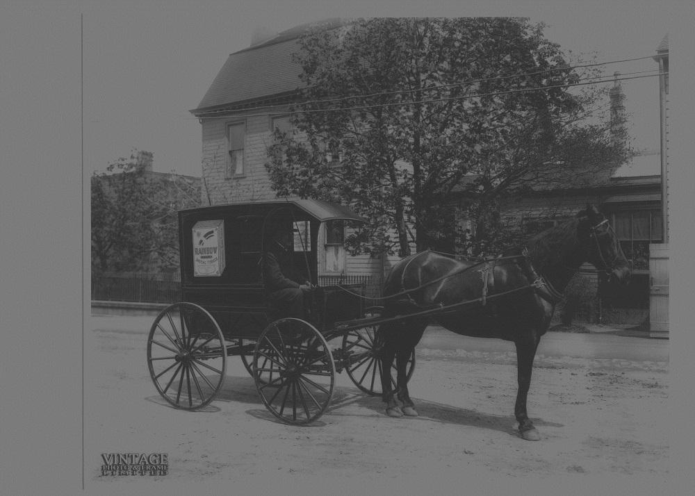 Photographie montrant un cheval attelé à un petit chariot portant la mention « Rainbow Smoking Tobacco ».