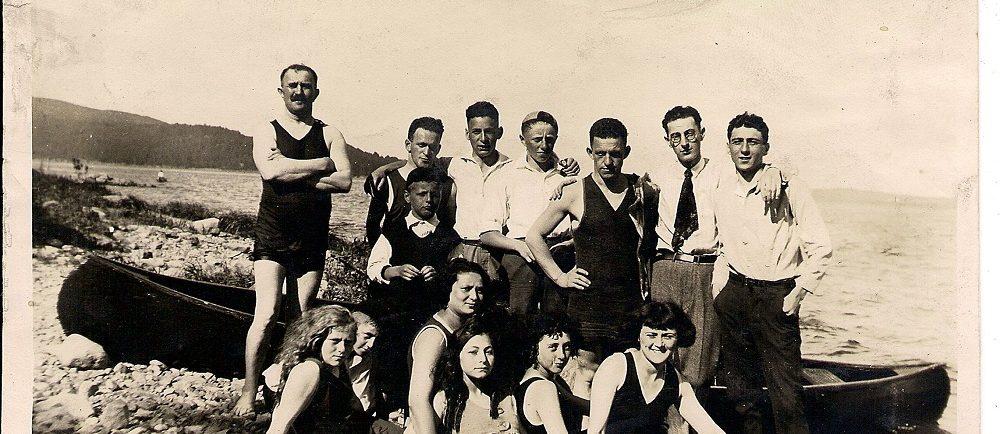 Treize amis, dont certains en maillot de bain et d'autres en pantalon et chemise rassemblés devant un canot sur une plage.