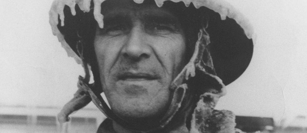 Photographie en noir et blanc d'un homme au visage paisible, arborant un uniforme de pompier couvert de glace.