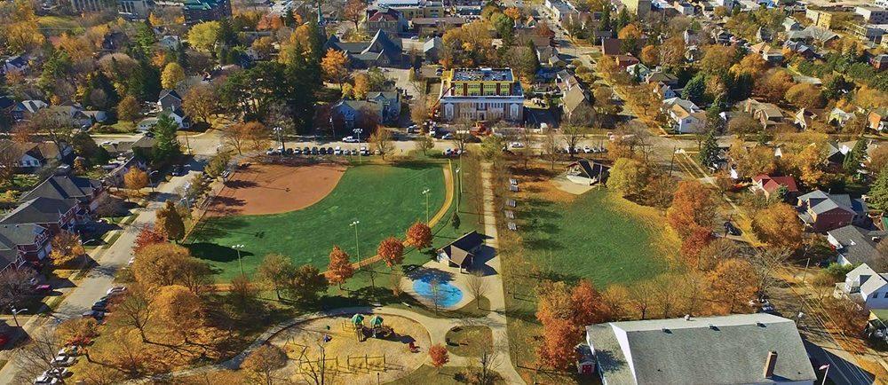 Photo couleur d'un parc en automne montrant un terrain de jeu et une fontaine à jets douchants dans le coin inférieur gauche, on voit une grand bâtiment blanc avec un toit gris dans le coin inférieur droit, un kiosque à musique couvert dans le coin supérieur droit et un terrain de baseball avec éclairage dans le coin supérieur gauche, des maisons et des bâtiments à l'arrière.