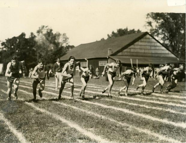 Photo en noir et blanc de neuf garçons en short et débardeur courant sur des pistes dans un parc.  Grand bâtiment en bois et quelques spectateurs et voitures à l'arrière.