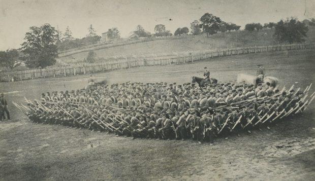 Photographie en noir et blanc de soldats en rangs serrés dans un champ, armés de fusils,  avec trois chevaux, deux assez flous, derrière deux hommes à gauche et au fond une ferme et une barrière en bois.