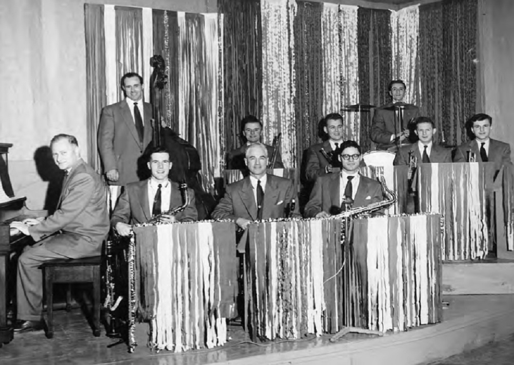Photo en noir et blanc un peu floue d'un orchestre de dix musiciens en costume, cravate, derrière des pupitres sur une estrade à deux niveaux.  Des bandes verticales de papier ou de tissu donnent un effet chatoyant.  A gauche un pianiste derrière son instrument.