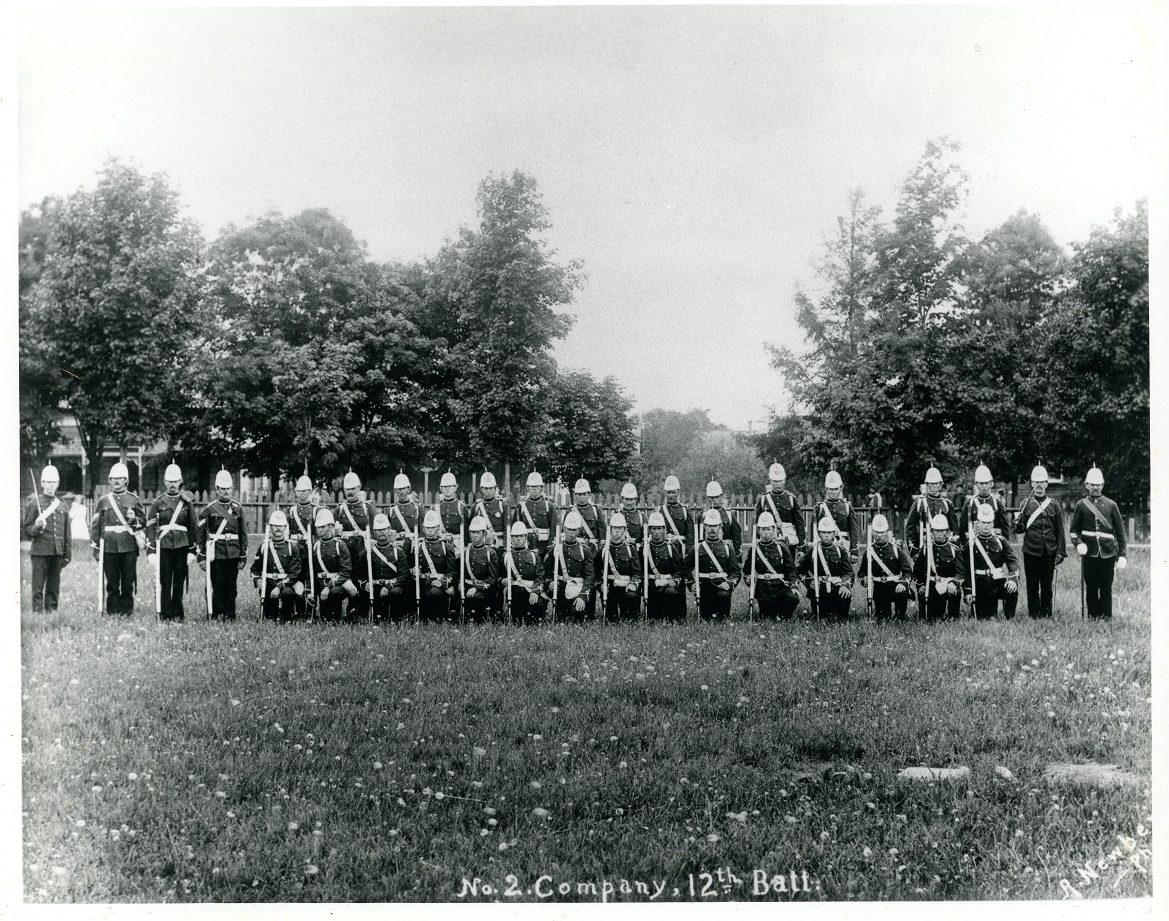 Photographie en noir et blanc de soldats dans un parc sur deux rangées, le genou droit à terre pour ceux de la première rangée.  Ils sont tous armés d'un fusil ou d'une épée et sont coiffés d'un casque à pointe ; au fond une clôture blanche, des arbres et des maisons.