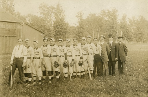Photographie en noir et blanc d'une équipe de 14 joueurs, certains avec des gants de baseball, d'autres avec une batte, dans un champ avec des arbres et un bâtiment en bois dans le fond.  Dix hommes portent un uniforme arborant le logo, « Best Everyday Shoe ».