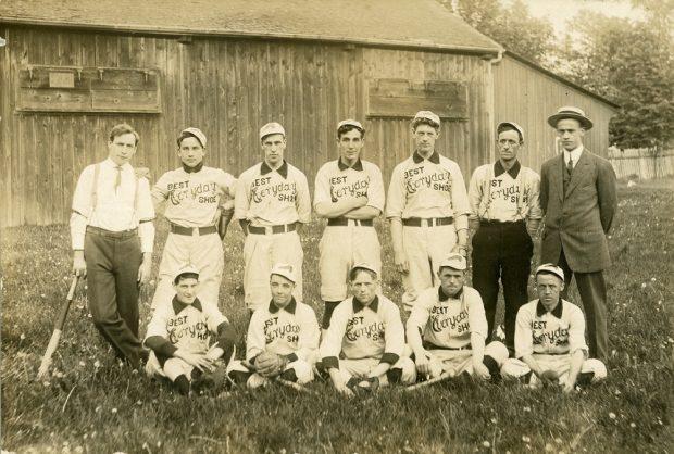 Photo en noir et blanc d'une équipe de joueurs de baseball sur deux rangées, le premier rang est assis sur l'herbe devant un bâtiment en bois ; Dix hommes en uniforme avec le logo « Best Everyday Shoe » sur leur jersey et deux hommes en costume de ville de chaque côté de la rangée arrière.