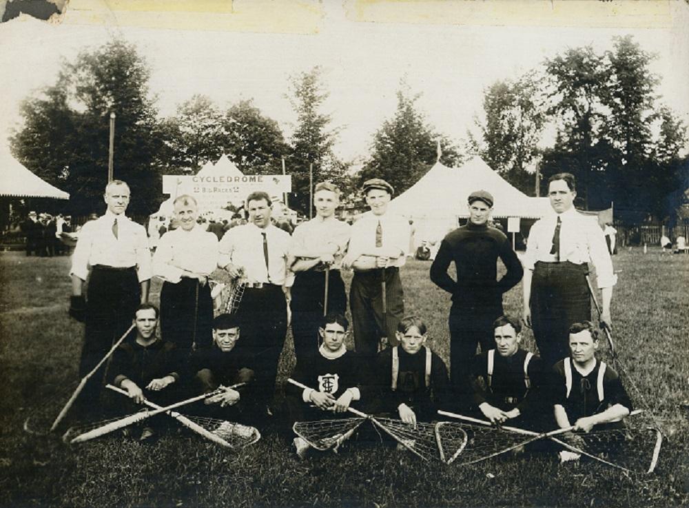 Photo en noir et blanc d'une équipe de la crosse sur deux rangées dans le parc municipal, devant six hommes assis sur la pelouse avec des crosses sur les genoux, derrière sept hommes, à l'arrière, parc avec trois grandes tentes blanches entourées de gens.