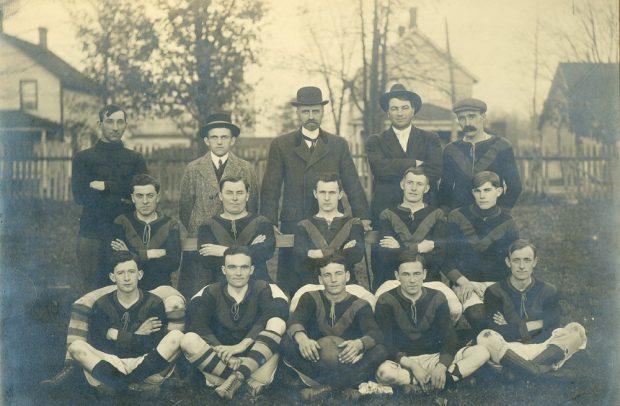 Photographie en noir et blanc d'une équipe de foot sur trois rangées, cinq joueurs sont en uniforme, l'un au milieu tient une balle, cinq joueurs sur la deuxième rangée sont assis sur un banc, sur la  dernière rangée, on voit  cinq joueurs debout avec au fond quatre maisons et une clôture en bois