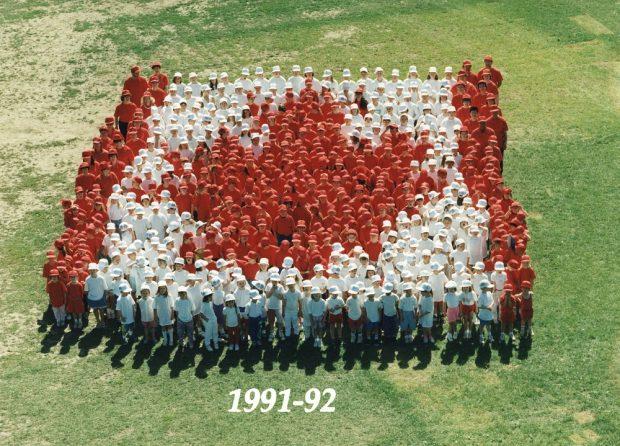 Photo en couleur vue d'en haut montrant un groupe d'élèves habillés en rouge ou en blanc debout sur l'herbe et formant un drapeau canadien.