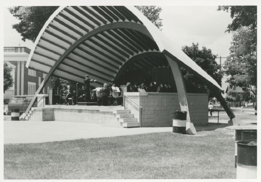 Photo en noir et blanc d'un abri d'orchestre avec une scène en ciment surélevée et 5 marches de chaque côté.  Toit de forme parabolique avec deux arches.  Un orchestre est en train de jouer.