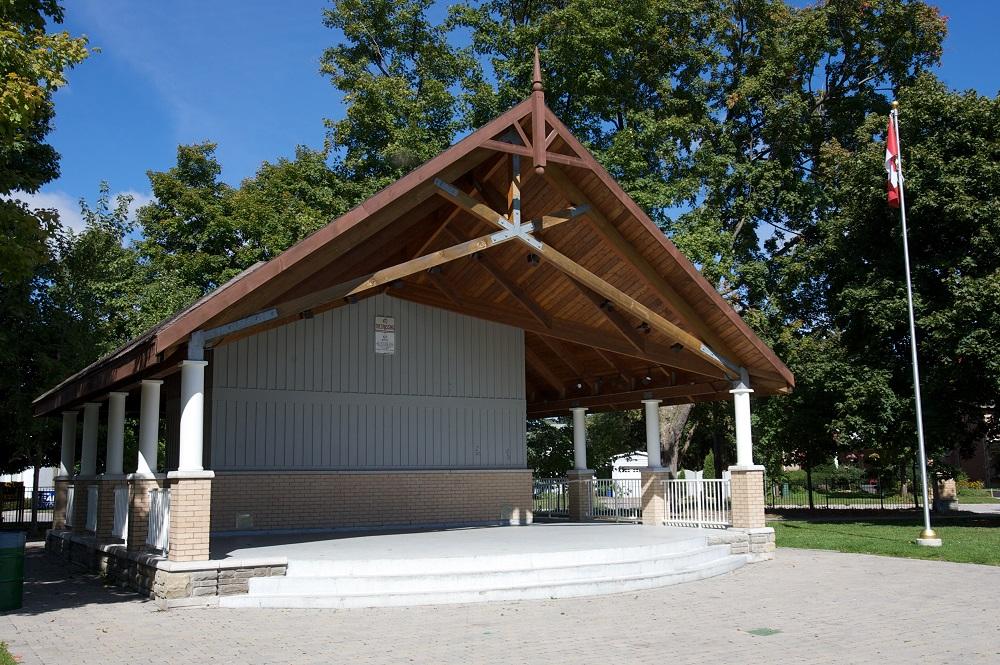 Photo en couleur d'un kiosque à musique couvert de forme carrée avec une estrade en ciment,  10 colonnes supportant un toit en bois et une structure en bois et en brique.  Il y a un drapeau canadien sur un poteau près du coin droit.  On voit à l'arrière de l'herbe, des arbres et une clôture.