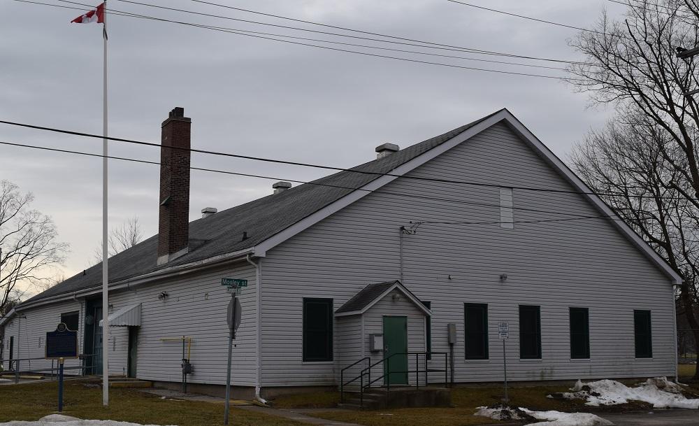 Photo en couleur d'un bâtiment blanc avec un toit en pente, on voit aussi un mât, une plaque commémorative et des plaques pour les rues Mosley et Larmont dans le coin inférieur gauche.
