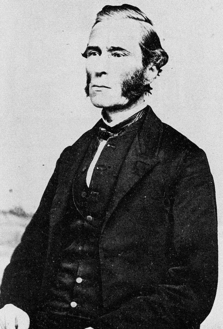 Photo en noir et blanc d'un homme à partir de la taille, arborant des favoris, portant une veste sombre, un gilet, des pantalons, une chemise blanche et une cravate noire.