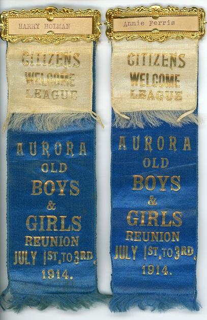 Paire de rubans de soie bleue recouverts d'un ruban de soie crème avec des lettres dorées et au dessus un cadre doré rectangulaire contenant un morceau de papier avec un nom.