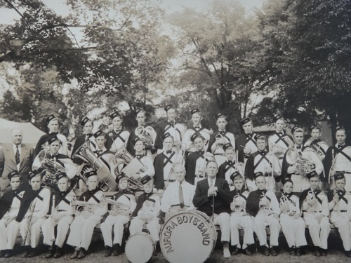 Photographie en noir et blanc d'un orchestre dans un parc avec trois rangées de jeunes musiciens en uniforme dont la plupart tiennent un instrument.  Au premier rang des musiciens assis dans un parc.