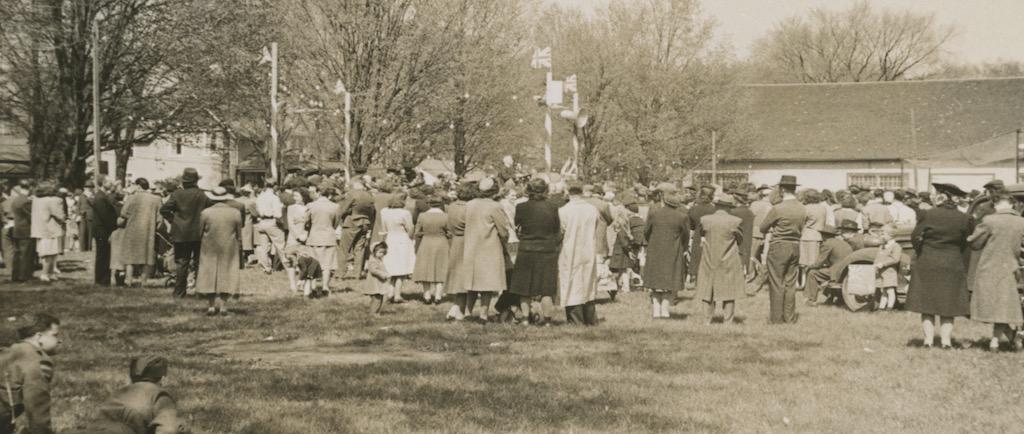 Photo un peu floue en noir et blanc d'un grand rassemblement de gens, beaucoup tournant le dos à l'appareil photo.  Douze personnes dans un parc  sont assises sur une estrade à gauche, quatre poteaux arborent  l'Union Jack et on voit des arbres et des maisons à l'arrière.