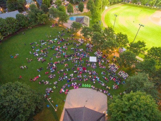 Photo en couleur prise par un drone qui montre un grand parc avec une scène couverte, une fontaine avec des jets douchants et un terrain de baseball.  La pelouse est remplie de gens qui regardent la scène assis sur des chaises ou des bancs.