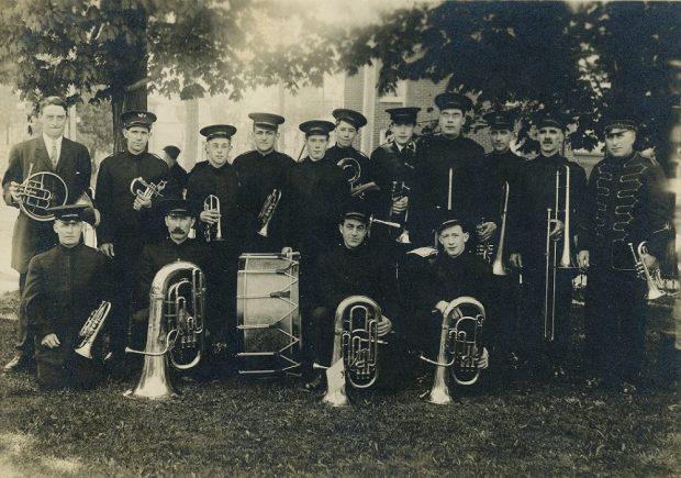 Photo en noir et blanc de 15 musiciens en uniforme  avec leur instrument sous les arbres.  Les musiciens de la première rangée sont à genoux.