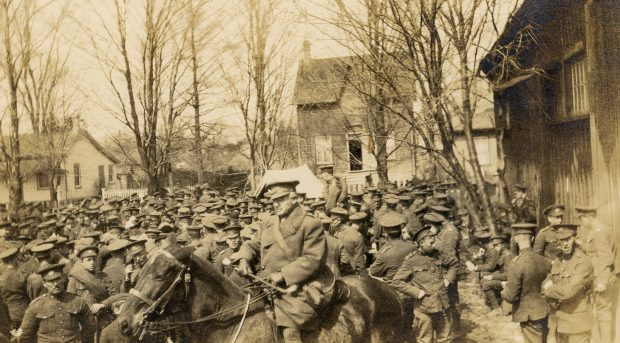 Photo en noir et blanc d'un large groupe de soldats à gauche d'un bâtiment en bois.  Officier à cheval et arbres et maisons à l'arrière.