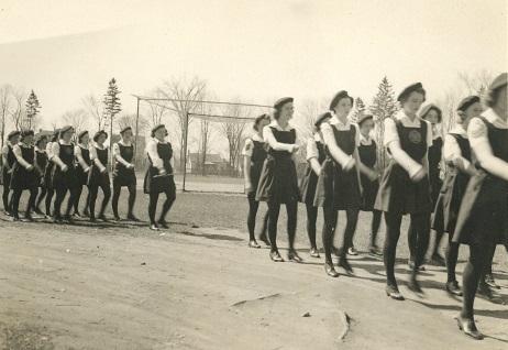 Photo en noir et blanc montrant des filles en uniforme défilant dans un parc.  Au fond, terrain de baseball et maisons