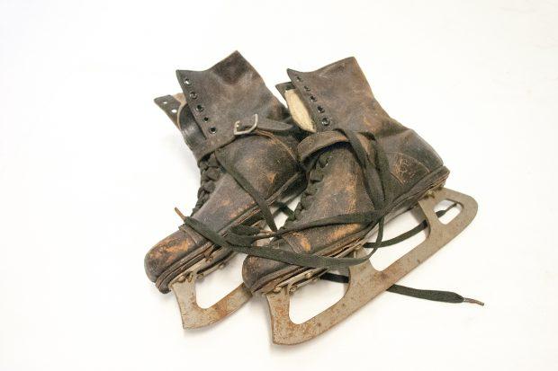 Paire de patins, chaussures en cuir brun foncé avec lanière devant la cheville, doublure moletonnée,  lames rouillées.