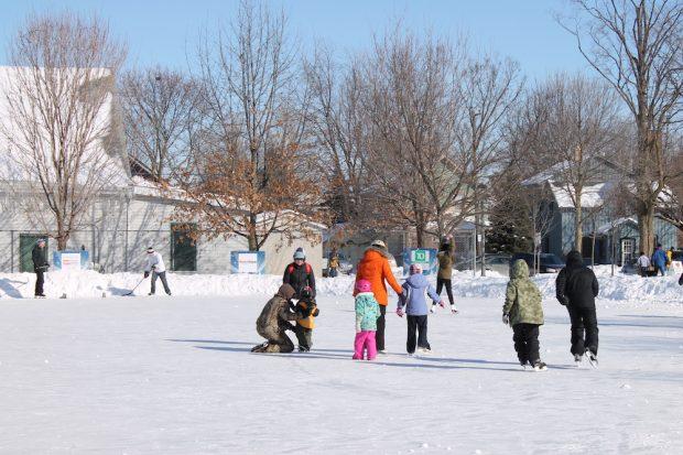 Photo en couleur prise en hiver montrant des gens de tous les âges patinant sur la patinoire en plein air.  Deux patineurs tiennent un bâton de hockey, à  gauche une clôture devant un  grand bâtiment, deux maisons à droite.