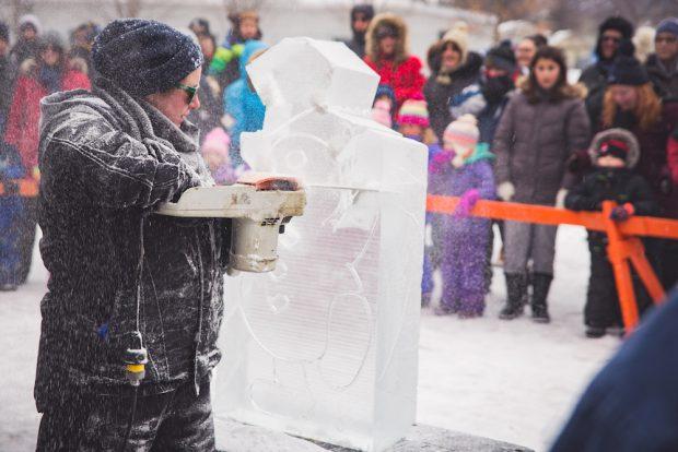 Photo couleur prise pendant les mois d'hiver montrant une femme utilisant une tronçonneuse pour sculpter un bonhomme de neige dans un gros bloc de glace.  L'arrière-plan est flou mais on voit des adultes et des jeunes, habillés pour l'hiver, rassemblés derrière une grande barricade orange vif.