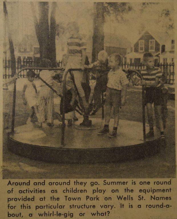 Image sépia, noire et grise de neuf enfants  sur un manège dans un parc.  A l'arrière une clôture en bois et des maisons.  Il y a une petite légende en noir sous l'image.