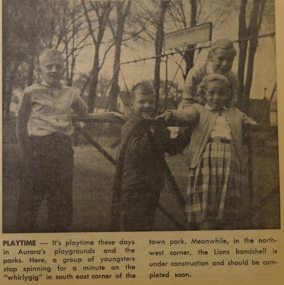 Une photo sépia, noir et gris montrant trois garçons et une fille adossés contre une structure métallique.  Au fond, des balançoires et des arbres.  Petit texte en noir sous l'image.