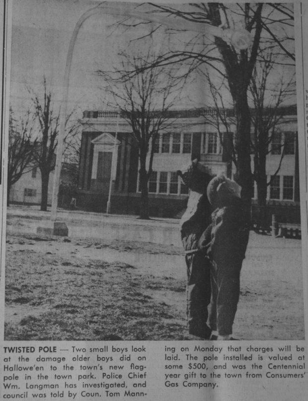 Photo en noir et blanc de deux jeunes garçons à droite dans un parc portant leur regard vers un très grand mât penché et arrivant à quelques mètres de leur tête, la base du mât sur la gauche.  À l'arrière un grand bâtiment de deux étages.  Légende en noir et blanc sous l'image.