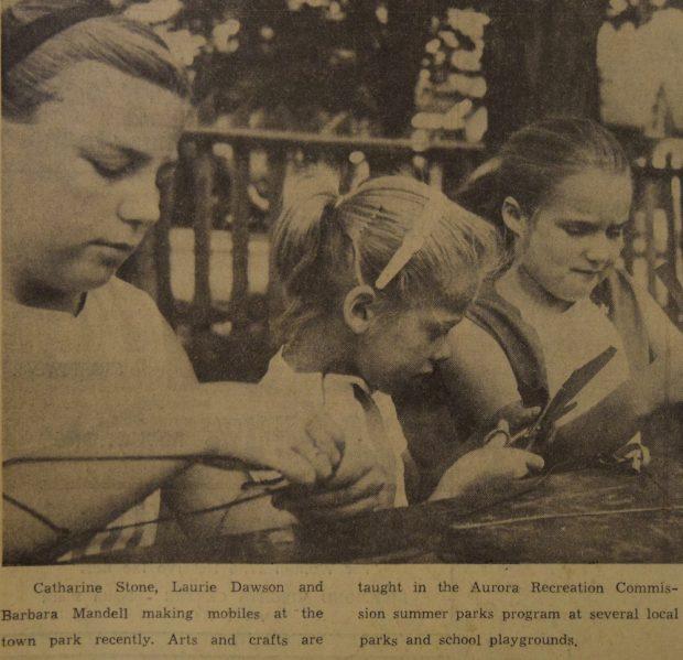 Image sépia et noir de trois filles qui utilisent une table à l'extérieur pour faire leur bricolage.  Petite légende en noir sous l'image.