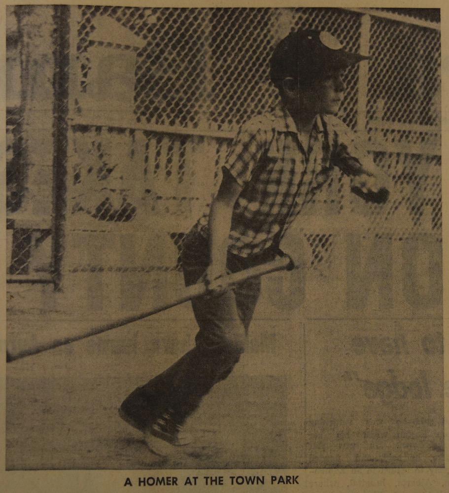 Image en sépia et noir d'un jeune garçon jouant au baseball.  Il tient une batte juste après avoir frappé une balle.  Il regarde au loin et on dirait qu'il s'apprête à courir.  On voit une clôture métallique à l'arrière et une petite clôture en bois.  Courte légende en noir sous l'image.