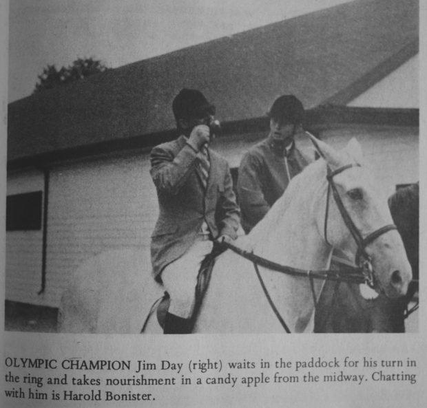 Photo en noir et blanc de deux cavaliers.  Ils portent une  bombe noire et les vêtements d'équitation de rigueur à l'époque.  L'homme à droite mange une pomme d'amour.  A l'arrière un grand bâtiment et une légende sous l'image.