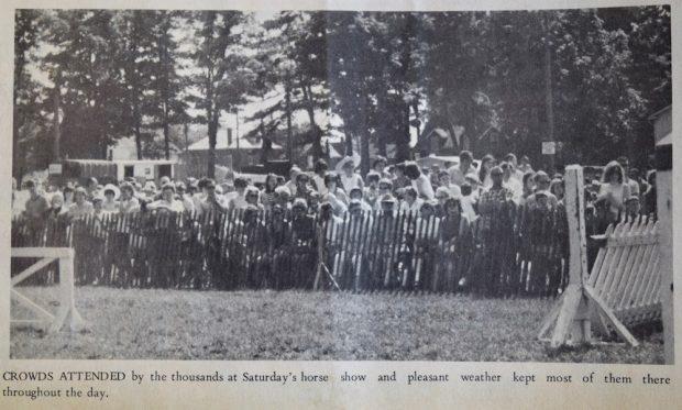 Image en noir et blanc avec une foule nombreuse dans le lointain derrière une clôture en bois.  Derrière de grands arbres et des maisons.  Devant, des structures en bois à droite et à gauche.  Légende sous l'image.