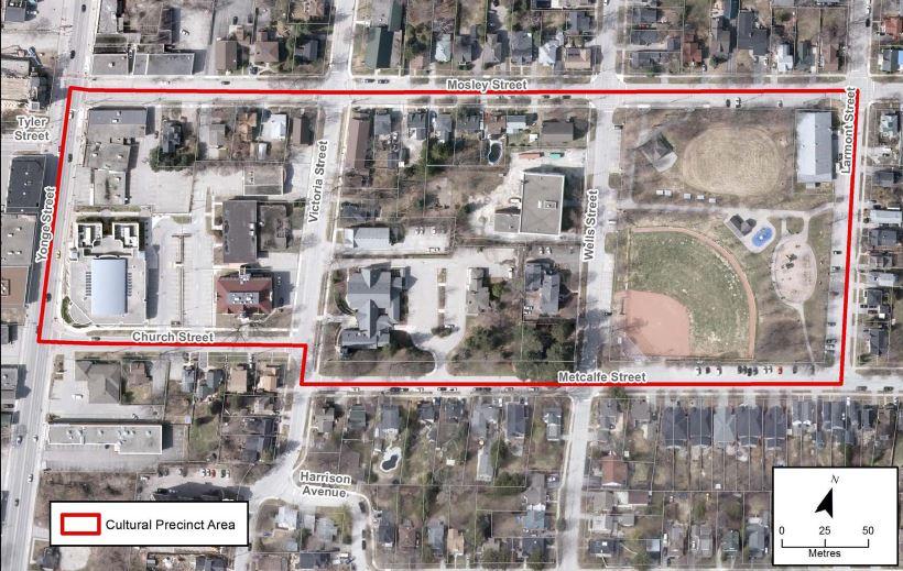 Une photo aérienne en couleur montre les trois pâtés de maison de la zone culturelle entourée de rouge, on voit le nom des rues et les distances dans le coin inférieur droit.
