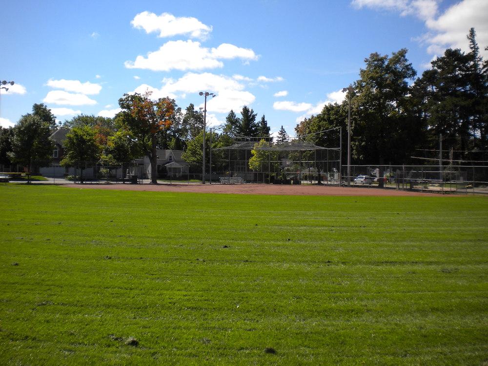 Photo en couleur du champ extérieur d'un terrain de baseball du côté du marbre.  On voit surtout la pelouse du champ extérieur, la terre rougeâtre du champ intérieur et une clôture derrière.