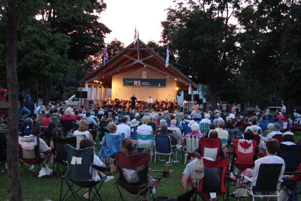 Photo en couleur de gens assis devant des musiciens qui jouent dans l'abri d'orchestre au crépuscule.