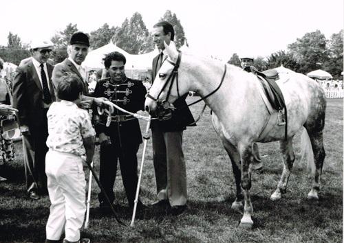 Photo en noir et blanc de 5 personnes et d'un cheval dans un parc, arbres et tentes au fond.