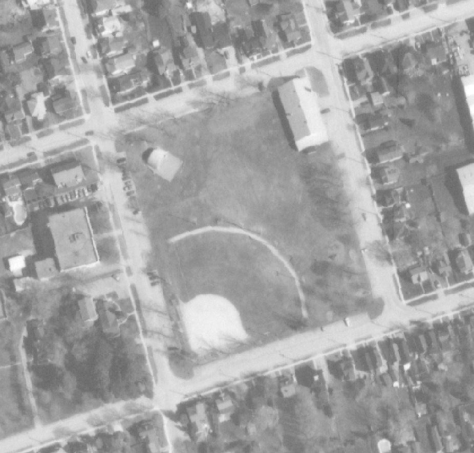 Photo aérienne en noir et blanc montrant un terrain de baseball, un abri d'orchestre et un manège militaire ainsi que les rues et maisons avoisinantes.
